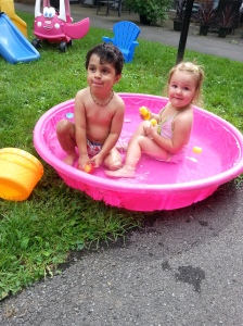 Playing with his girlfriend in the kiddie pool